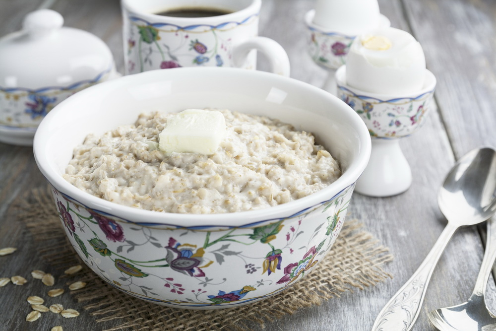 Porridge with butter and eggs on the wooden table